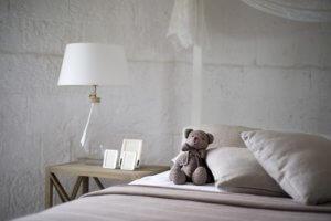 Bett mit Tedybär und nachttisch Kissen schlafen schlafzimmer